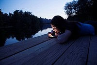 A woman using an electronic organizer while lying on a jetty, dusk