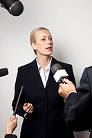A woman in a suit talking to the media