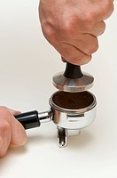 Professional preparation of espresso with an espresso machine: The tamper is carefully set on the coffee grounds