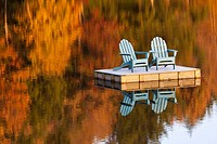 two adirondack chairs on dock in autumn