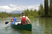 Couple, man and woman, canoeing, paddling, upper Liard River, Pelly Mountains behind, Yukon Territory, Canada