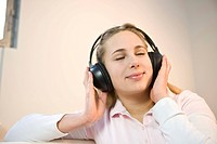 Relaxed teenage girl listening to music on a headphone