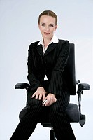 Woman sitting on an office chair, holding a mobile phone