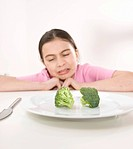 Girl sitting in front of a plate of broccoli with a disgusted look on her face