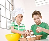 Girl wearing a chef's hat and a boy cracking eggs into a bowl