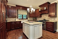 Kitchen in luxury home with white and granite island