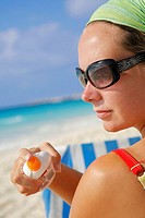 Woman in sunglasses applying suntan lotion on a Caribbean beach