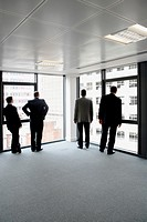 Business men looking out of the windows at the view in a new office development