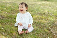 Japan, Saitama Prefecture, Baby girl sitting on grass, laughing