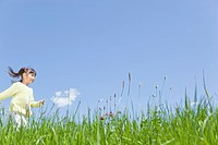 Japan, Tokyo Prefecture, Girl running in meadow, side view