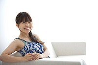 Japan, Osaka Prefecture, Woman sitting on sofa, smiling, portrait