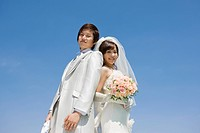 portrait of a smiling bride and groom against blue sky