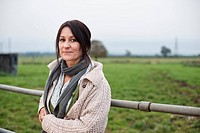 woman leaning on farm fence