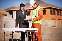 2 men examining plans on worksite