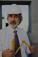 Construction supervisor holding folding ruler, portrait