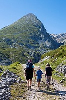 Family hiking in the Ándara massif, mountain of La Pica de Mancondiu in background. Picos de Europa National Park, Cantabria, Spain