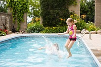 Sisters jumping into swimming pool, Mount Albert, Ontario