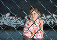 Little girl with broken arm behind fence with graffiti in background