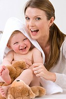 Mother hugging laughing baby boy with towel on head