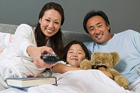 Family Watching TV Together in Bed mother using remote control
