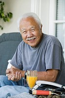 Senior man with orange juice outdoors portrait