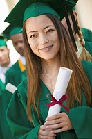 Graduate Holding Diploma outside with others behind portrait