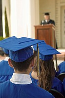 Graduates listening to speaker outside back view