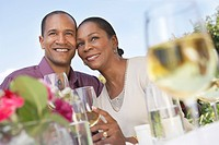 Elegant couple cheek to cheek holding wine glasses at garden party table