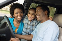 Family smiling together on driver's seat close_up