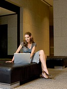 Woman using laptop in lobby (thumbnail)