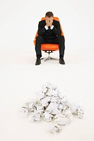 Frustrated businessman sitting near pile of crumpled paper (thumbnail)