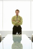 Businessman with arms crossed at conference table portrait