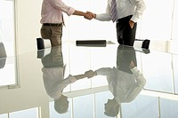 Businessmen shaking hands by conference table mid section