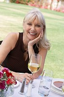 Mature elegant woman sitting at table outdoors (thumbnail)