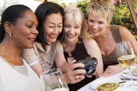 Four elegant women at garden party looking at photos on digital camera (thumbnail)