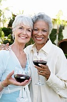 Middle_aged Friends standing outside Drinking Wine from wineglasses