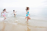 Children running in surf