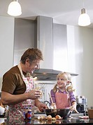 Girl 3_4 and father baking in kitchen