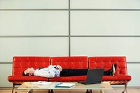 Businessman Lying on Modern Sofa in office