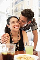 Young couple at sidewalk cafe man kissing woman portrait