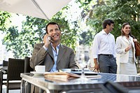 Businessman using mobile phone at outdoor cafe (thumbnail)