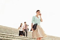Three office workers walking down steps woman in foreground using mobile phone low angle view