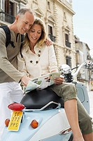 Couple With Scooter Reading Map on old street in Granada Spain