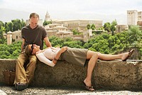 Tourist Couple Relaxing on Wall in Granada Spain
