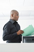 Office worker reading file in office side view