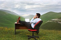 Businessman with feet on desk in mountain field talking on phone side view