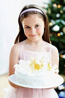 Girl holding Snowflake-Decorated Cake in living room (thumbnail)