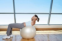 Woman Doing Sit_Ups on exercise ball in gym