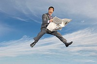 Business man reading newspaper mid-air outdoors (thumbnail)