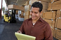 Warehouse Worker in front of man working with forklift